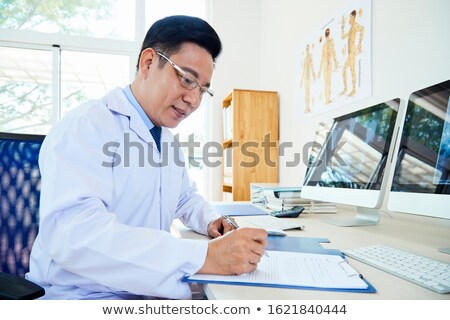 Stock photo: male doctor working with desktop at his desk