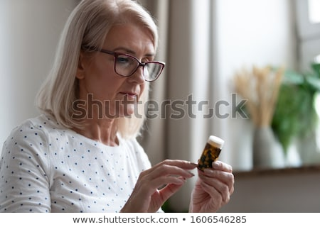 Older woman holding a pill Stock photo © photography33