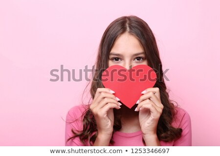 Female holding a pink paper heart Stock photo © stockyimages