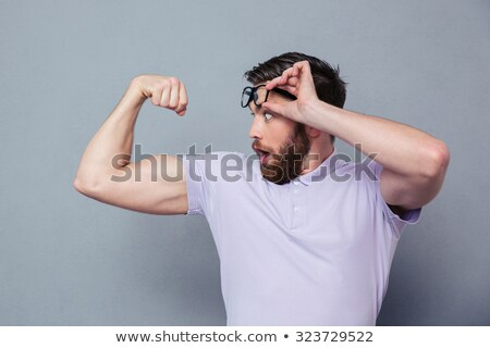 Portrait of confident muscular man flexing his biceps on black background