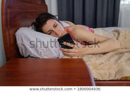Portrait of a brunette turning off her alarm clock in her bedroom Stock photo © wavebreak_media