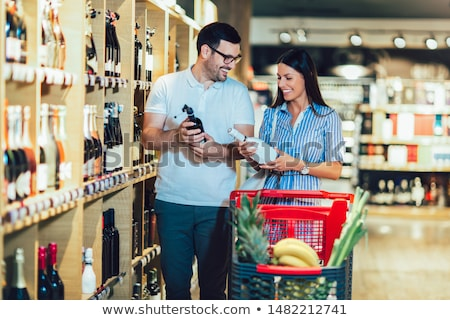 young couple chooses the wine at supermarket stock photo © hasloo