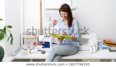 female tailor sitting at her workplace with notebook stock photo © deandrobot