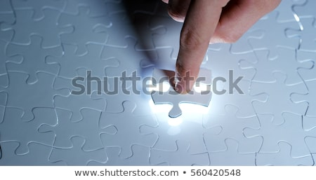 Businessman hand putting a missing piece into jigsaw puzzle Stock photo © stevanovicigor