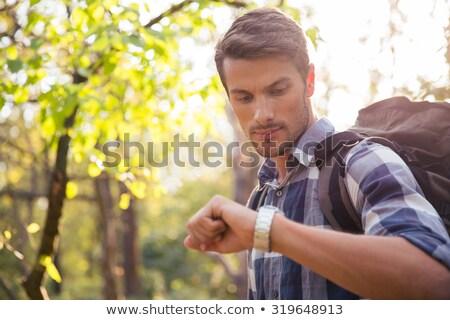 Male hiker looking on wrist watch Stock photo © deandrobot
