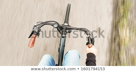 Stock photo: Hands of a man on mountain bicycle handlebars.