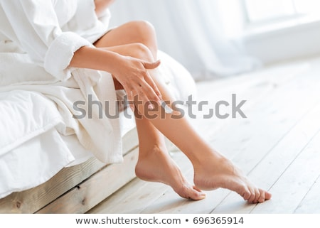Woman Applying Body Lotion In The Bathroom Stock photo © dash