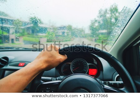 Hands of woman driver driving on road in rainy weather Stock photo © deandrobot