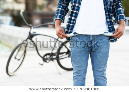 upset casual man showing his empty pockets stock photo © deandrobot