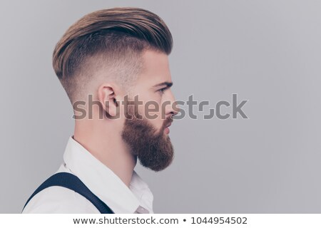 Handsome serious concentrated bearded young businessman Stock photo © deandrobot