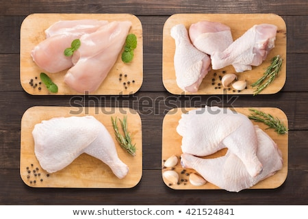 Raw uncooked chicken legs, drumsticks on wooden board, meat with ingredients for cooking, top view stock photo © yelenayemchuk