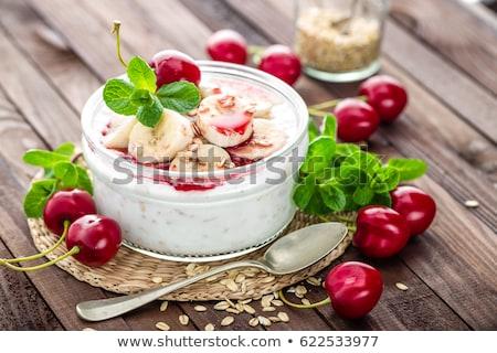 Fresh yogurt with cherry, banana and oats, healthy breakfast Stock photo © yelenayemchuk