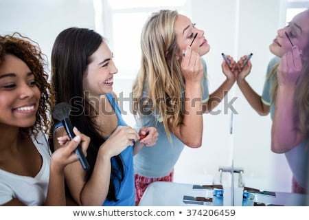 Girl putting make-up on friend Stock photo © IS2
