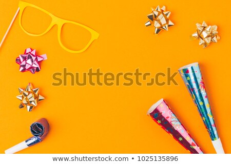 flat lay with various party objects and party mask isolated on orange Stock photo © LightFieldStudios