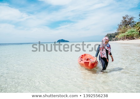 Woman dragging her boat to the water on the beach Stock photo © Kzenon