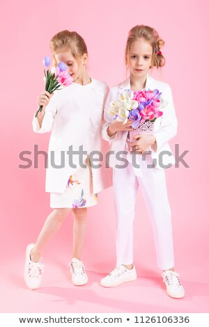 Twins girls in light clothes with bouquets of flowers stand on a pink background. Stock photo © Traimak