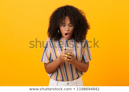 shocked emotional african woman posing isolated over yellow background using mobile phone stock photo © deandrobot