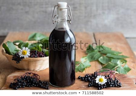 A bottle of black elder syrup with fresh elderberries stock photo © madeleine_steinbach