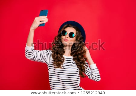 Beautiful brunette with red lips and wavy hair taking self portrait. Stock photo © studiolucky
