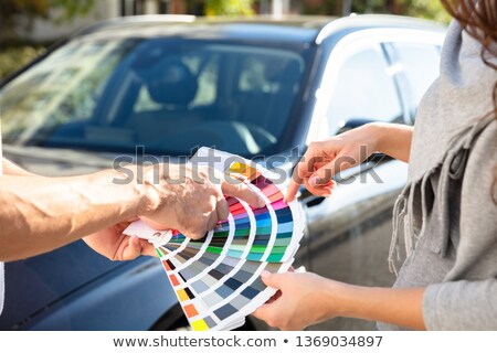 Stock photo: Man Showing Color Samples Standing In Front Of Car
