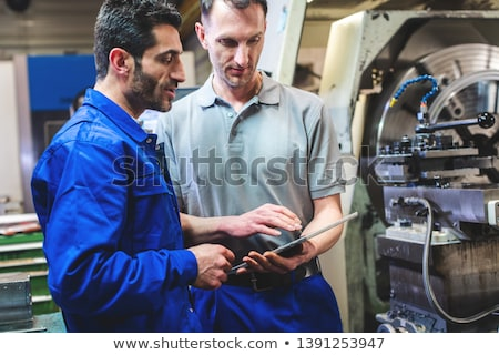 Two workers discussing a project in front of CNC lathe machine Stock photo © Kzenon