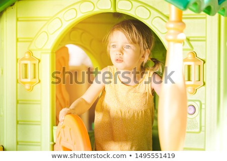 Little girl being absorbed playing in a hut Stock photo © Kzenon