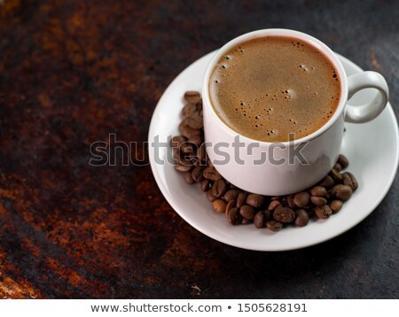 Cup of coffee and coffee beans closeup on iron rusty background Stock photo © butenkow