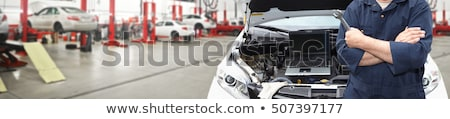 mechanic man with wrench repairing car at workshop Stock photo © dolgachov