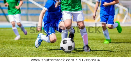 Young Boys In Football Teams Running in Duel After Soccer Ball Stock photo © matimix