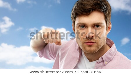 angry young man ready for fist punch over sky Stock photo © dolgachov