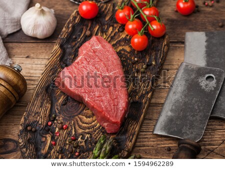 Slice of Raw Beef Topside Joint with Salt and Pepper on wooden chopping board with fork and knife, a Stock photo © DenisMArt