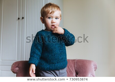Portrait of handsome blonde little child keeps finger in mouth, looks with his blue appealing eyes,  Stock photo © vkstudio