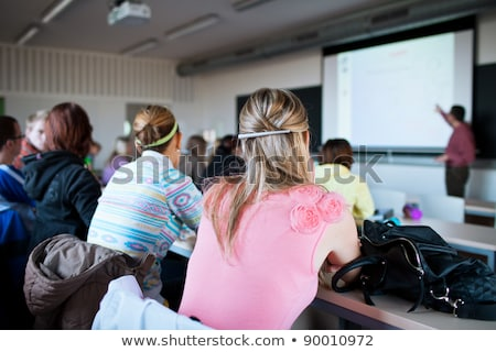 young, pretty female college student sitting in a classroom full Stock photo © lightpoet