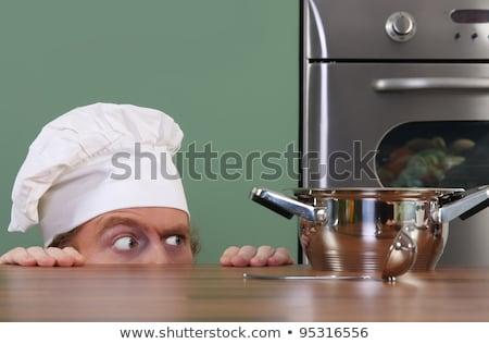 Engraçado jovem chef estranho olhando pote Foto stock © vladacanon