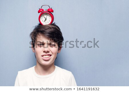 boy irritated with noise of alarm clock stock photo © stockyimages