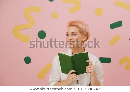 cute young woman covering her face with a book she is reading stock photo © lightpoet