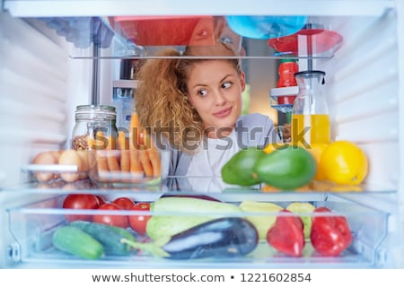 young woman looking for something to eat inside the fridge stock photo © amok