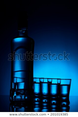 Many glasses of vodka lit with blue backlight stock photo © dla4