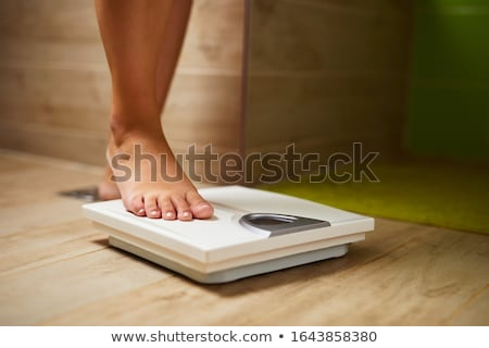 Foto stock: Overweight Woman Weighing Herself On Scales In Bathroom