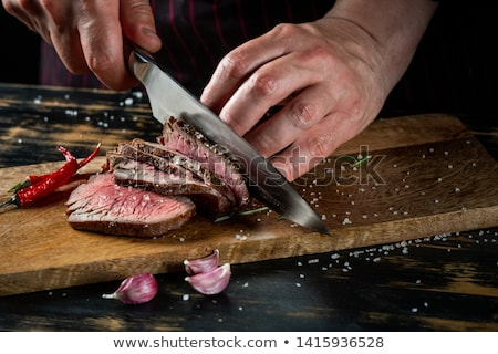 cook cuts meat fillet on a table stock photo © oleksandro