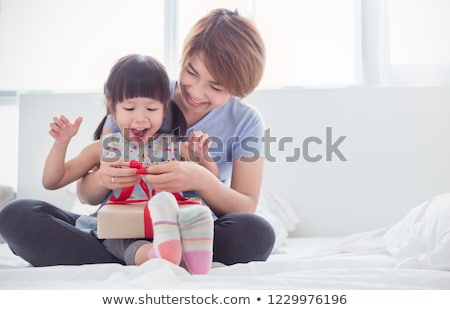 Mother Helps to Unwrap Birthday Present Stock photo © dash