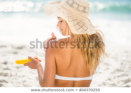 happy woman in swimsuit with sunscreen on beach stock photo © dolgachov