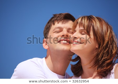 Attractive pair against blue sky, touching by cheeks