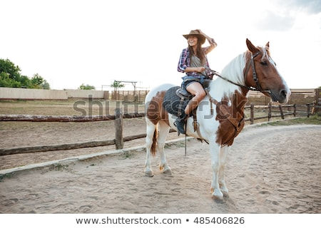 Smiling woman cowgirl sitting and riding horse on ranch Stock photo © deandrobot