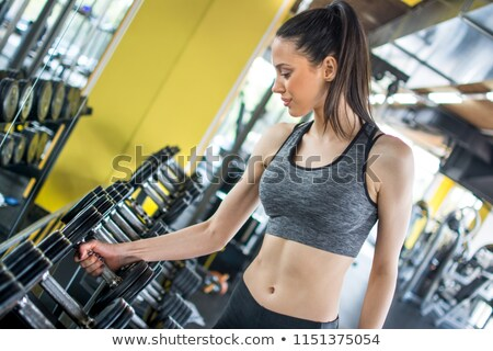 Young woman choosing dumbbells in gym Stock photo © chesterf