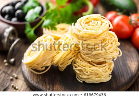 Raw all'uovo pasta, egg noodles with cooking ingredients on dark wooden rustic background, tradition Stock photo © yelenayemchuk