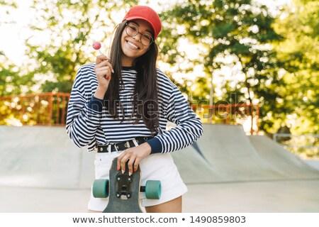молодые красивая женщина очки скейтборде Сток-фото © deandrobot