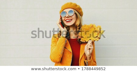 cheerful young lady wearing sunglasses talking by mobile phone stock photo © deandrobot