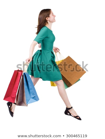 side view of woman in dress walking and looking behind stock photo © feedough
