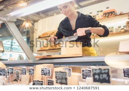 Young shop clerk in deli cutting cheese Stock photo © Kzenon